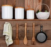 Closeup of a rustic kitchen wall. One shelf with canisters and a basket. Hanging on the wall below a