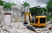 foto of excavator  - A compact excavator on a small domestic building site where a breezeblock building has just been demolished - JPG
