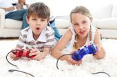 stock photo of video game  - Animated children playing video games lying on the floor - JPG