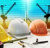 image of engineering construction  - safety helmet on architect engineer working table with modern building and crane construction background use for construction business and civil engineering real estate topic - JPG
