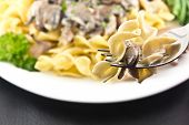 picture of crimini mushroom  - Hearty mushroom Stroganoff with egg noodles on the tip of a fork ready to eat