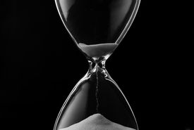 foto of countdown timer  - Sand trickling through the bulbs of an hourglass or egg timer measuring the passage of time on a dark background - JPG