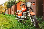stock photo of generic  - Old Red Motor Cycle Parked On Green Grass Yard - JPG
