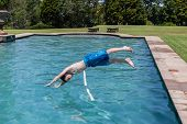 stock photo of playtime  - Boys diving into swimming pool home summer playtime - JPG