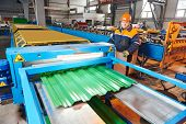 picture of manufacturing  - industrial worker operating metal sheet profiling mechine at manufacturing factory - JPG
