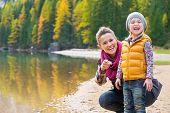 stock photo of south tyrol  - Portrait of smiling mother and baby on lake braies in south tyrol italy - JPG