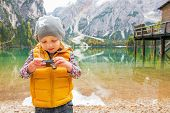 picture of south tyrol  - Child checking photos in camera on lake braies in south tyrol italy - JPG