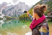 picture of south tyrol  - Young woman taking photo on lake braies in south tyrol italy - JPG