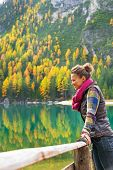 stock photo of south tyrol  - Young woman with on lake braies in south tyrol italy looking into distance - JPG