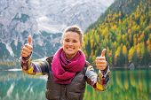 pic of south tyrol  - Happy young woman on lake braies in south tyrol italy showing thumbs up - JPG