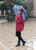 picture of dancing rain  - Woman with an umbrella standing smiling and enjoying the rain - JPG