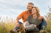 picture of married couple  - Portrait Of A Happy Mature Couple Sitting In Field And Contemplate The Future - JPG