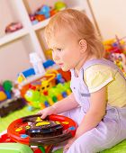 foto of daycare  - Portrait of cute little baby girl sitting in playing room - JPG