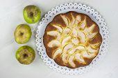 stock photo of pie-in-face  - Homemade italian baked apple pie over a white table - JPG