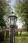 stock photo of crossed swords  - Lamp in churchyard at Appledore Kent UK with crossed swords on the glass - JPG