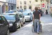 image of rollator  - boy is pushing his friend on a wheelchair - JPG