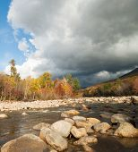pic of loon  - Sun highlights the autumn trees while dark clouds gather over the scenic cool Pemigewasset River Route 112 Bear Notch Kancamagus Highway - JPG