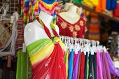 image of dress mannequin  - Red yellow green dress on white mannequin in clothing market - JPG