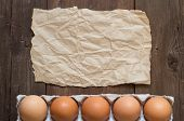 stock photo of paper craft  - Chicken eggs in the package and craft paper on the old wooden table - JPG