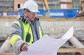 image of inspection  - Civil Engineer at at construction site is inspecting ongoing production according to design drawings - JPG