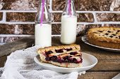 stock photo of cherry pie  - Homemade cherry pie with milk on wooden table - JPG