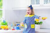 image of healthy eating girl  - Little girl preparing breakfast in white kitchen. Healthy food for children. Child drinking milk and eating fruit. Happy smiling preschooler kid enjoying morning meal cereal banana and strawberry.