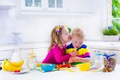 picture of little young child children girl toddler  - Little girl and boy preparing breakfast in white kitchen. Healthy food for children. Child drinking milk and eating fruit. Happy smiling preschooler kids enjoying morning meal cereal banana and strawberry. ** Note: Shallow depth of field - JPG