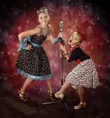 foto of rockabilly  - Rockabilly girls singing on a colorful background with glowing lights - JPG