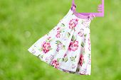 stock photo of habilis  - Fashion baby dress hanging on a hanger on a green background - JPG