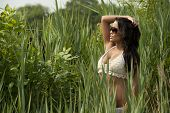 foto of one piece swimsuit  - A beautiful asian young female model standing in a grassy field on a sunny day wearing sunglasses and a 2 piece bathing suit - JPG