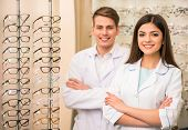 stock photo of optical  - Team of happy opticians optometrists standing in optical shop - JPG