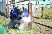 picture of erection  - welder outdoor working and soldering iron with mask - JPG