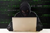 stock photo of hack  - hacker man in black hood and mask with computer laptop and dangerous dark look hacking system having access to data info and privacy in business digital cybercrime or cyber crime concept - JPG