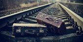 stock photo of old suitcase  - Two old vintage suitcases left on railway rails.