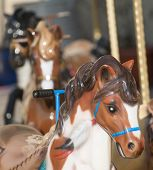 stock photo of carousel horse  - small caroussel horses outdoors in the sunshine - JPG