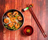 pic of rice noodles  - Vietnamese shrimp and rice noodles soup pho served on a wood table top - JPG