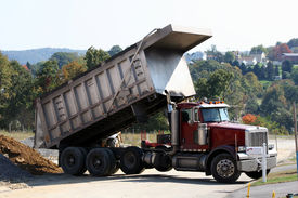 pic of dump_truck  - peterbilt dump truck dumping dirt at construction site - JPG