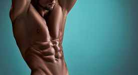 stock photo of body builder  - torso of attractive male body builder on blue background - JPG