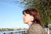 stock photo of average looking  - woman of average years looks at the river in spring afternoon - JPG