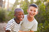Portrait of two boys embracing and laughing hard outdoors poster