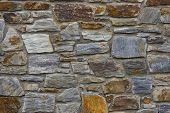 foto of wall-stone  - old stone wall using multi colored stones - JPG