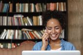 Beautiful Student Girl With Charming Smile Talking On Mobile Phone While Studying At College Library poster