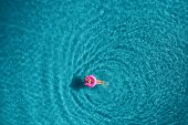 Aerial View Of Young Woman Swimming On The Pink Swim Ring poster