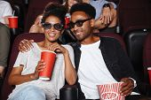 Happy afro american couple watching 3D movie and eating popcorn while sitting in a movie theater poster