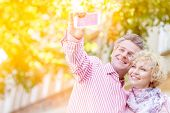 Happy middle-aged couple taking selfie through mobile phone outdoors poster