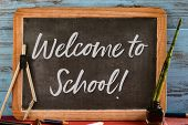 wooden-framed chalkboard with the text welcome to school written in it, on a rustic wooden table ful poster