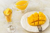 Mango Fruit Cubes And Mango Juice Puree On White Concrete Background. Tropical Fruit Concept. Vegan poster