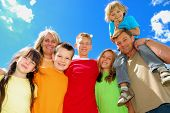 stock photo of family fun  - A happy family stands together under the clear sky posing happily - JPG