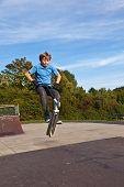 Постер, плакат: мальчик прыгает с его скутер в скейт парк