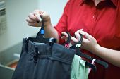 pic of shoplifting  - A female shop assistant at change room tags clothes for security - JPG
